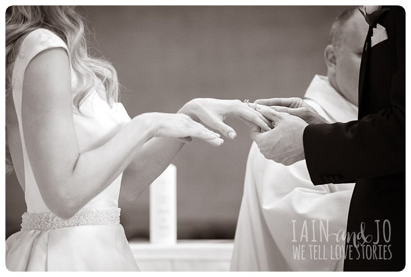 Groom Putting Wedding Ring On Bride's Finger During Ceremony